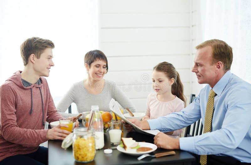 Tidningsläsning på frukosten royaltyfria bilder
