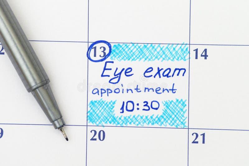 Tidsbeställning för påminnelseögonexamen i kalender med pennan arkivbild
