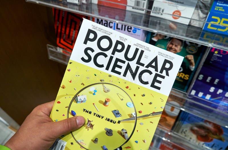 Tidskrift för populär vetenskap i en hand arkivfoto