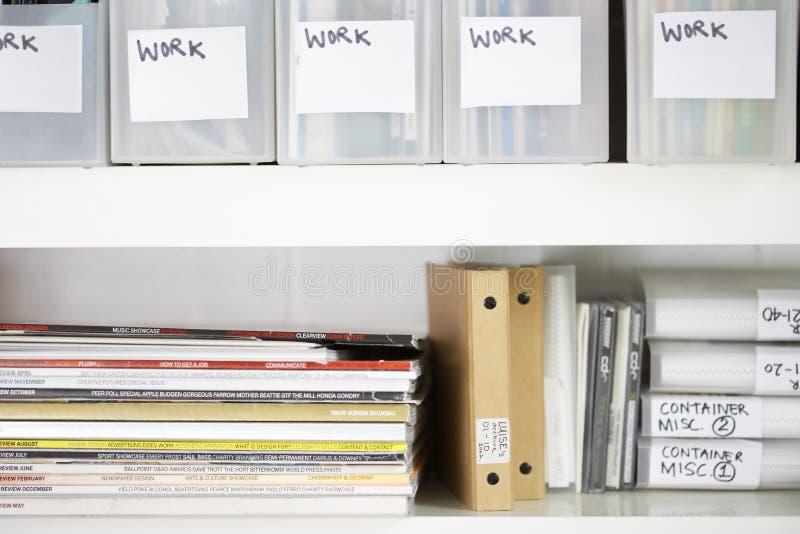 Tidskrifter och mappar i organiserade hyllor arkivfoto