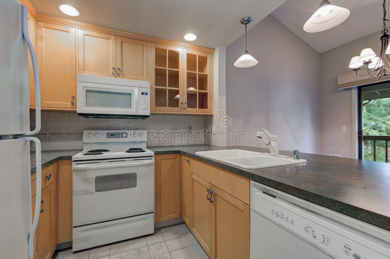 Tidy Compact Kitchen With Maple Cabinets, Dark Grey Counters, White  Appliances And Beige Tile Backsplash. Northwest, USA