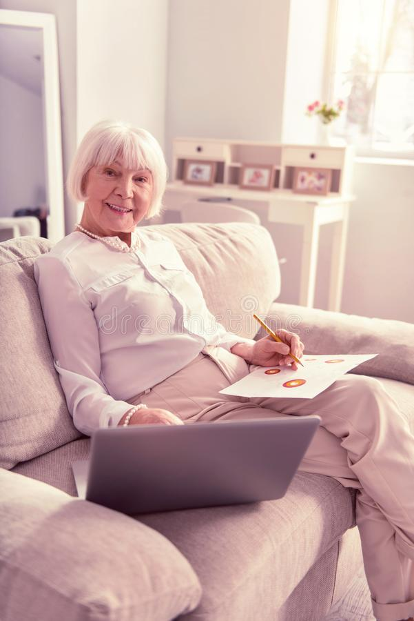 Tidy lady redrawing bright picture from laptop. Tidy lady redrawing. Tidy grey-haired lady redrawing bright picture from the laptop screen while resting on the royalty free stock photos