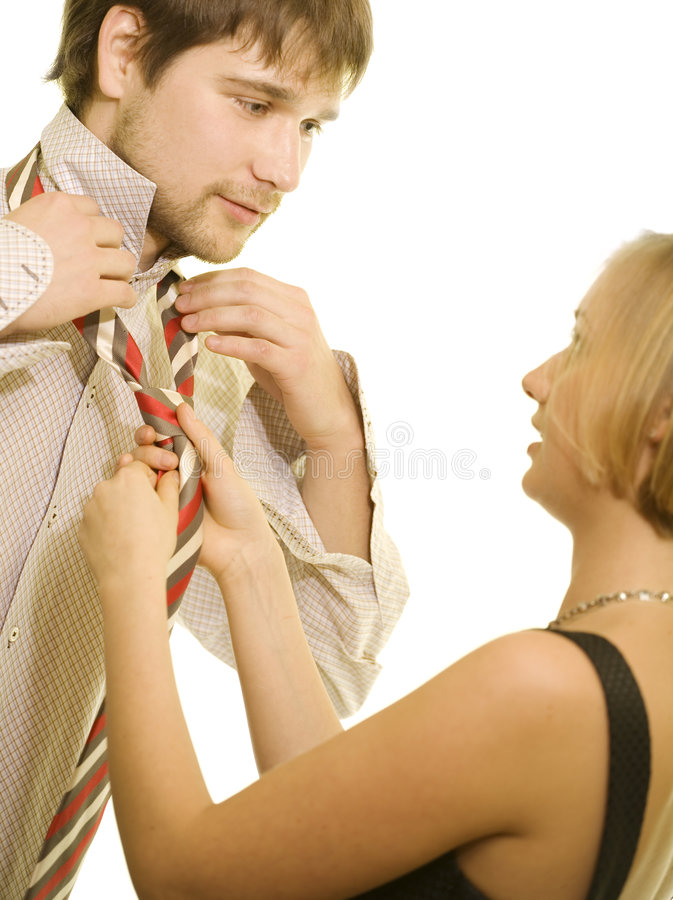 Tie. Young woman helps her man with the tie stock image