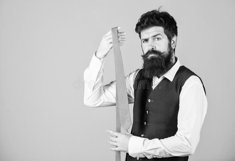 The tie is both stylish and elegant. Stylish businessman. Bearded man holding stylish necktie. Brutal guy wearing. Stylish clothes and accessory. Fashion model royalty free stock images