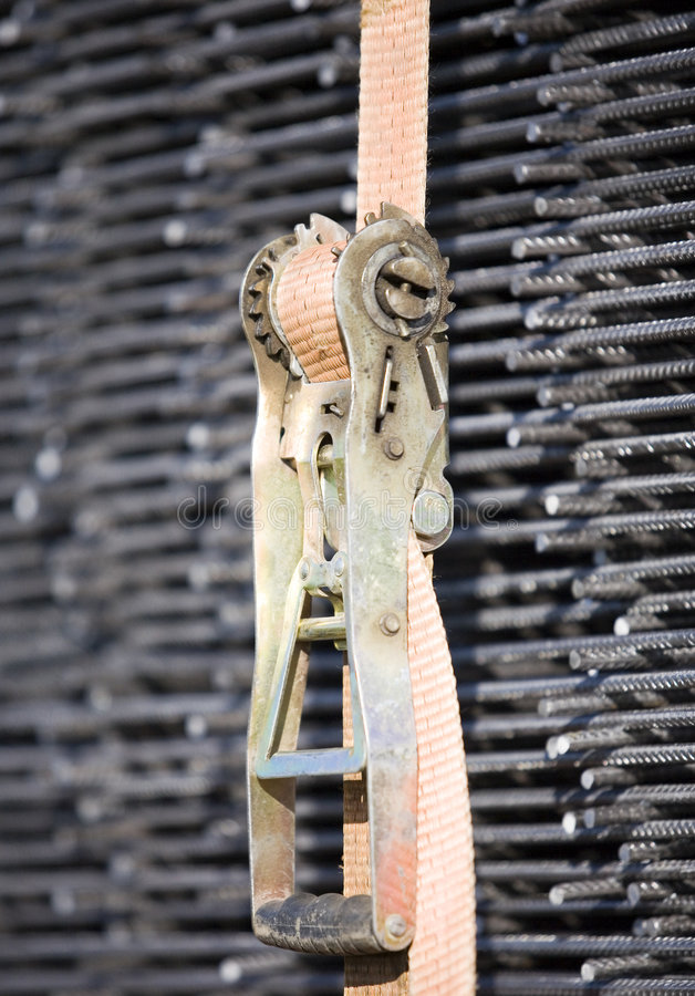 Tie down strap. A tie down strap holding steel together stock photo