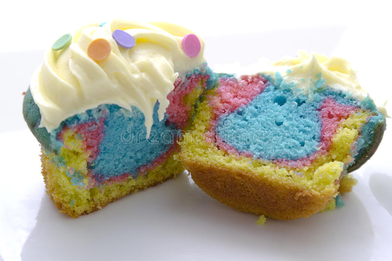 Tie dye cupcake. Cupcake cut in two with tie dye color inside royalty free stock photography