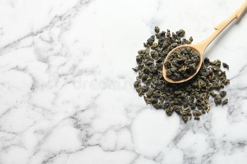 Tie Guan Yin oolong tea leaves and spoon on marble background, top view. Space for text stock photos