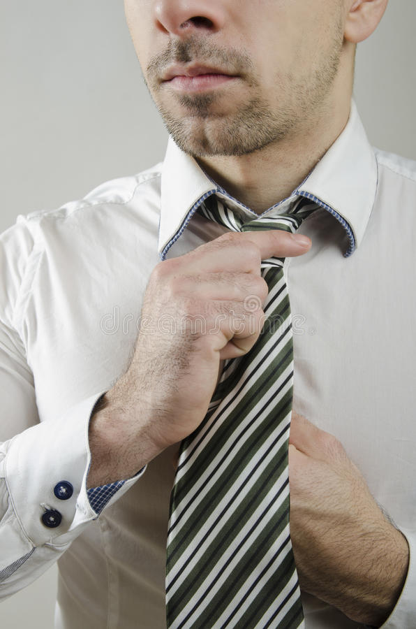 Tie knot. Anonymous guy doing a tie knot in closeup frame stock photography