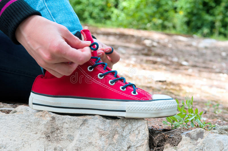 Tie shoelaces. Photo shows the girl in nature tying the laces on red sneakers stock photos