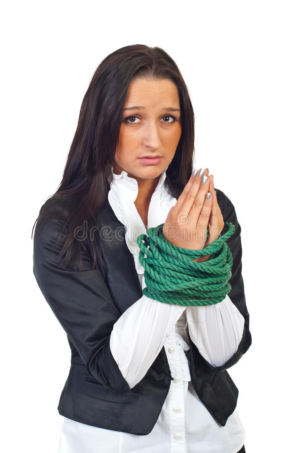 Tied businesswoman praying. Tied businesswoman with worried face praying isolated on white background stock photography