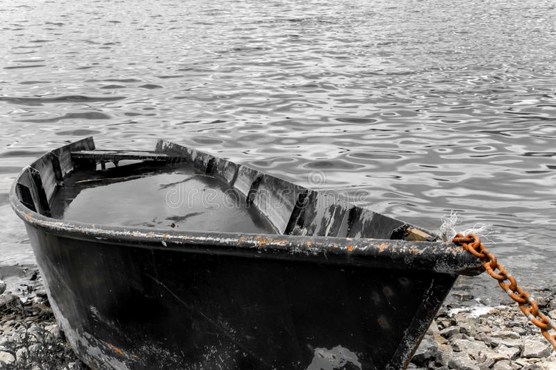 Fishing boat full of water on the shore stock image
