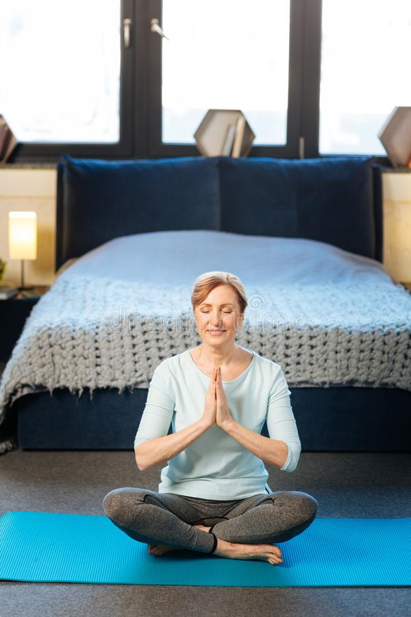 Tranquil mature woman in comfortable clothes doing yoga in her stylish apartment royalty free stock photo