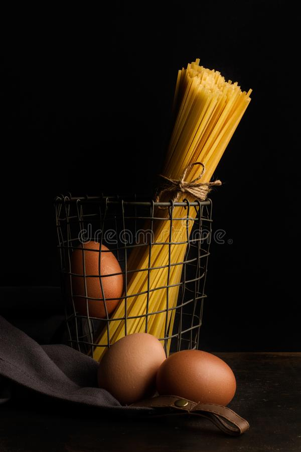 Tied raw noodles in a basket. And eggs on a dark background royalty free stock photo