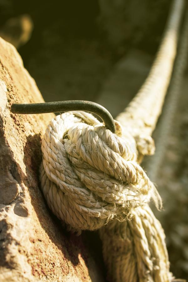 Tied thick cord or rope. Tick cord or a rope maybe from big ship or boat tied on the steel hook embarked in stone stock photography