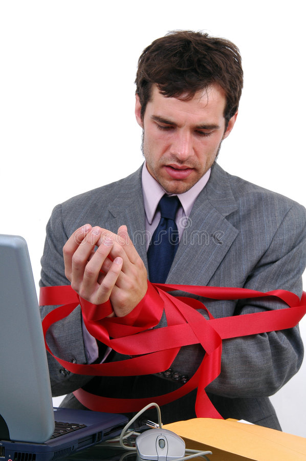 Tied Up. A businessman tied up in red tape stock photos