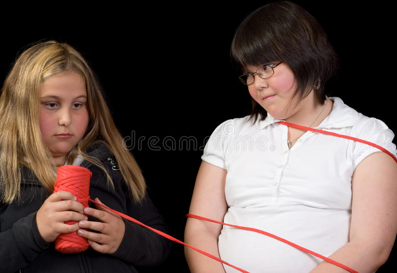 Tied Up. Two girl tying eachother up for fun, isolated against a black background royalty free stock photos