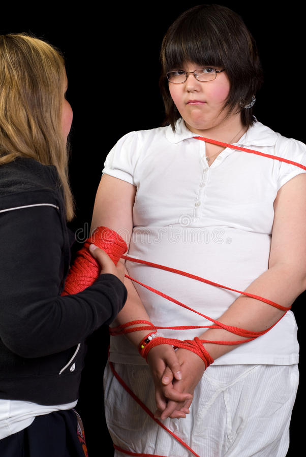 Tied Up. A young girl being tied up with rope by another girl royalty free stock photos