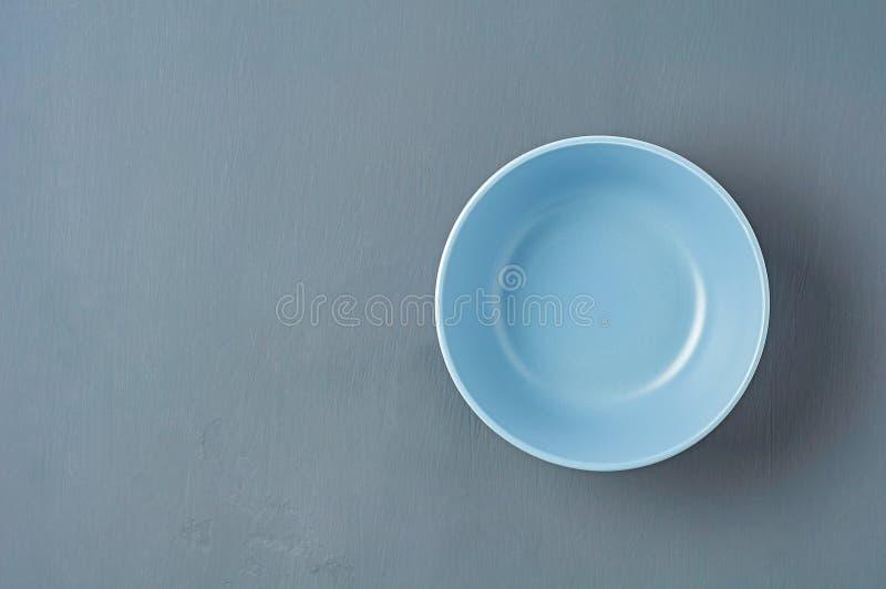 Tief leere, blaue Keramikschüssel liegt auf dunklem Beton. Textbereich lizenzfreie stockfotografie