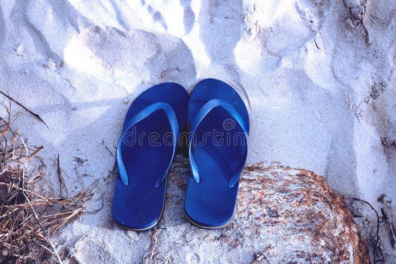 Tiefe blaue Farbpantoffel auf Strandsand lizenzfreie stockfotos