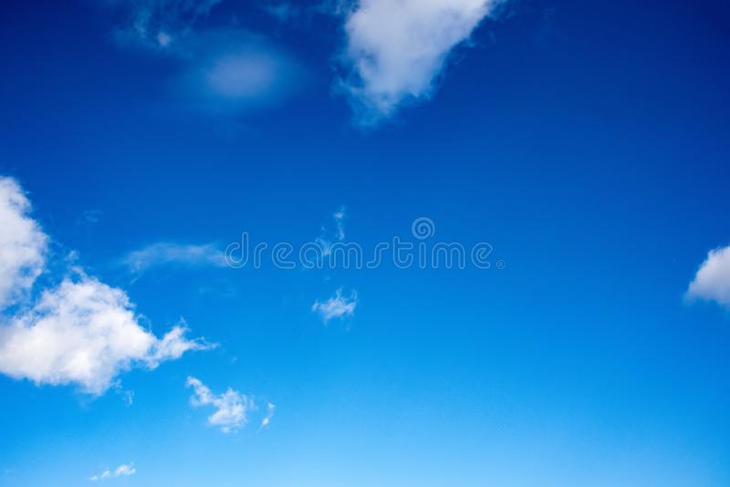 Tiefe blaue Himmel u. flaumige Wolken stockfotografie