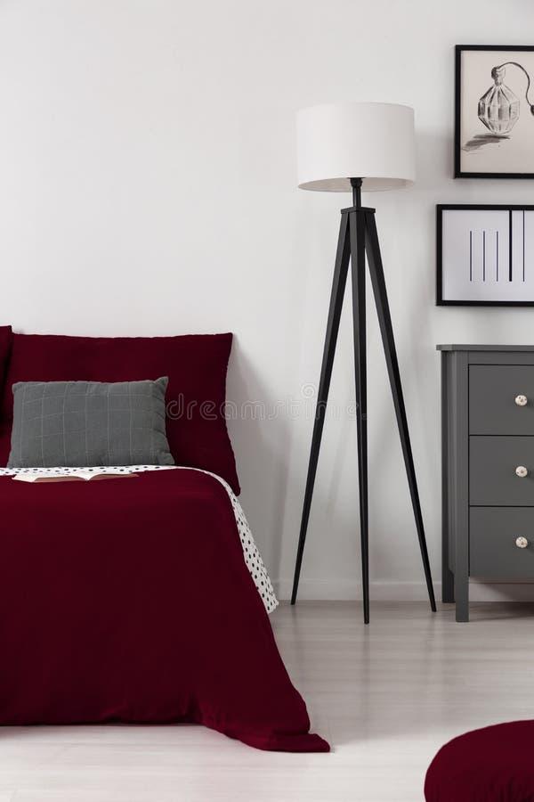 Tiefe Burgunder-Abdeckung auf einem Bett, das nahe bei einer modernen Schwarzweiss-Lampe in einem zeitgenössischen Schlafzimmerin lizenzfreie stockbilder