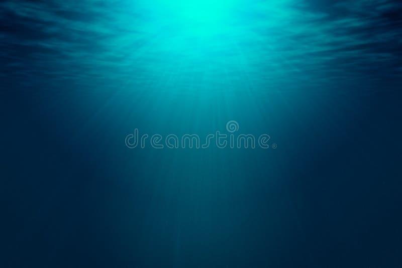 Tiefes blaues Meer mit Strahlen des Sonnenlichts, Ozeanoberfläche gesehen von Unterwasser stockfotos