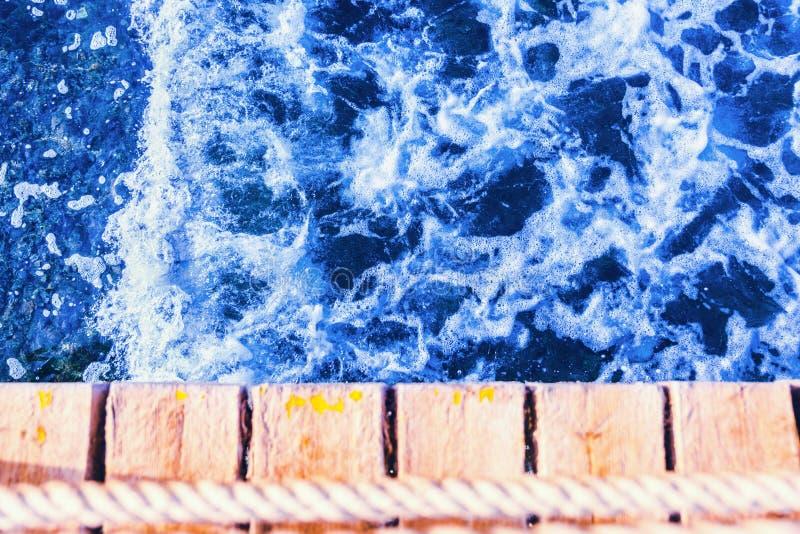 Tiefes blaues vibrierendes Meerwasser mit hölzernem Pier lizenzfreies stockfoto