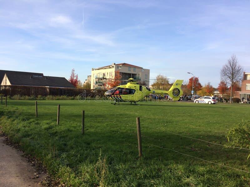 TIEL NEDERLÄNDERNA - NOVEMBER 14, 2018: Gul medicinsk helikopter som hjälper i medicinskt hjälpmedel i bostadsområde royaltyfria bilder