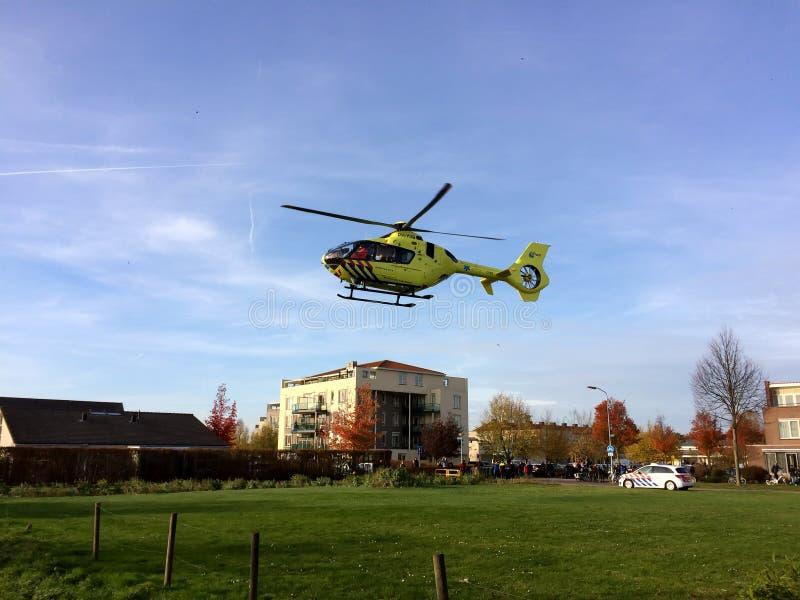 TIEL NEDERLÄNDERNA - NOVEMBER 14, 2018: Gul medicinsk helikopter som tar av, når att ha hjälpt i medicinskt hjälpmedel i bostadso royaltyfri bild