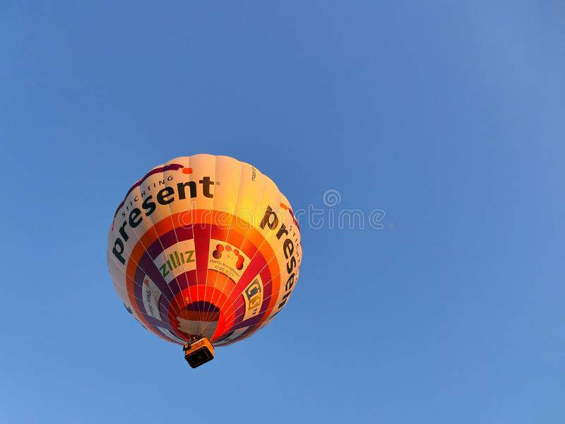 TIEL, THE NETHERLANDS - JULY 14, 2018: Hot air balloon with people flying in a blue sky shot from below. TIEL, THE NETHERLANDS - JULY 14, 2018: Red and white hot royalty free stock photography