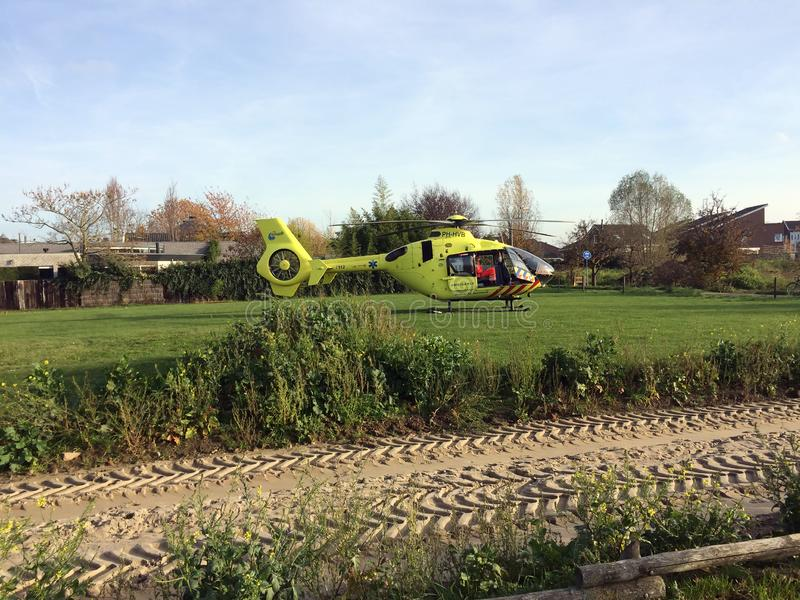 TIEL, THE NETHERLANDS - NOVEMBER 14, 2018: Yellow medical helicopter landed to assist in medical aid in residential area. In the Netherlands. Landed in a green stock image