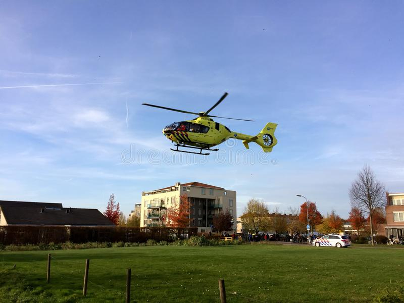 TIEL, THE NETHERLANDS - NOVEMBER 14, 2018: Yellow medical helicopter taking off after assisting in medical aid in residential area. In the Netherlands. Taking royalty free stock image