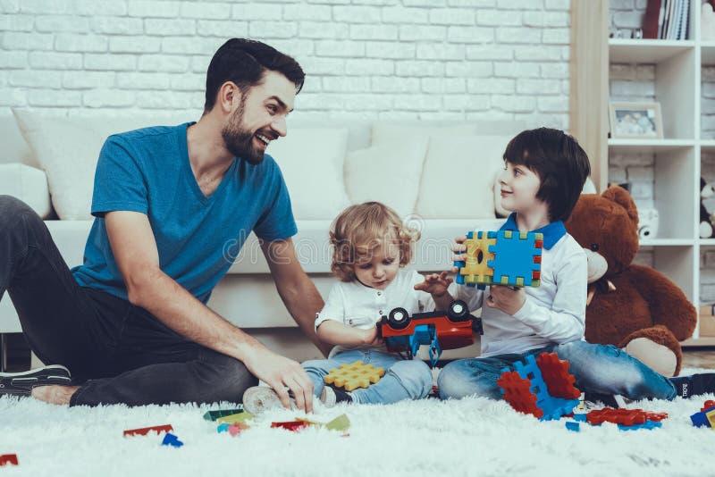 Tiempo casero feliz junto Cabritos sonrientes padre imágenes de archivo libres de regalías