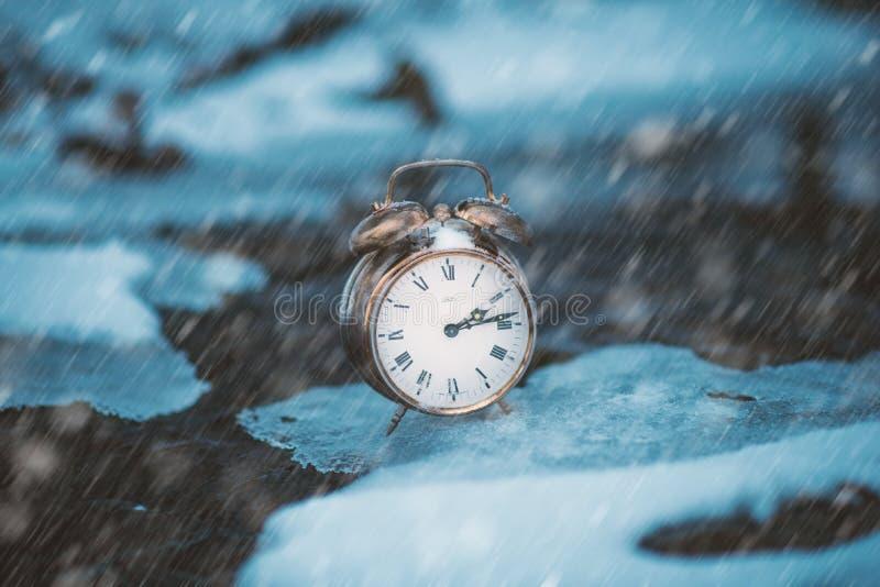 Tiempo congelado Un reloj en un hielo al lado del agua Situación extrema del tiempo Nieve que cae en un reloj en una naturaleza imágenes de archivo libres de regalías