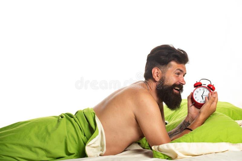 Tiempo de activación. Foto de un hombre guapo sosteniendo Alarm. Dormido sin dormir y cansado en la cama. Concepto de trastornos  fotos de archivo libres de regalías