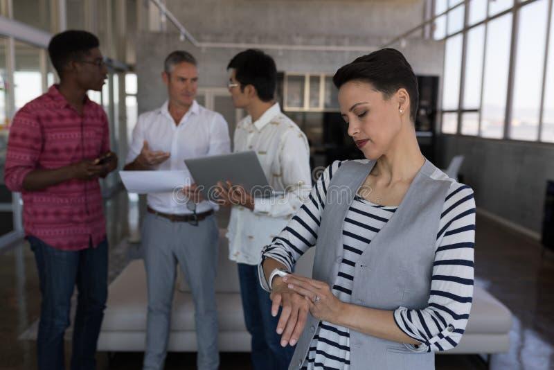Tiempo de comprobación ejecutivo femenino en smartwatch en oficina fotos de archivo libres de regalías