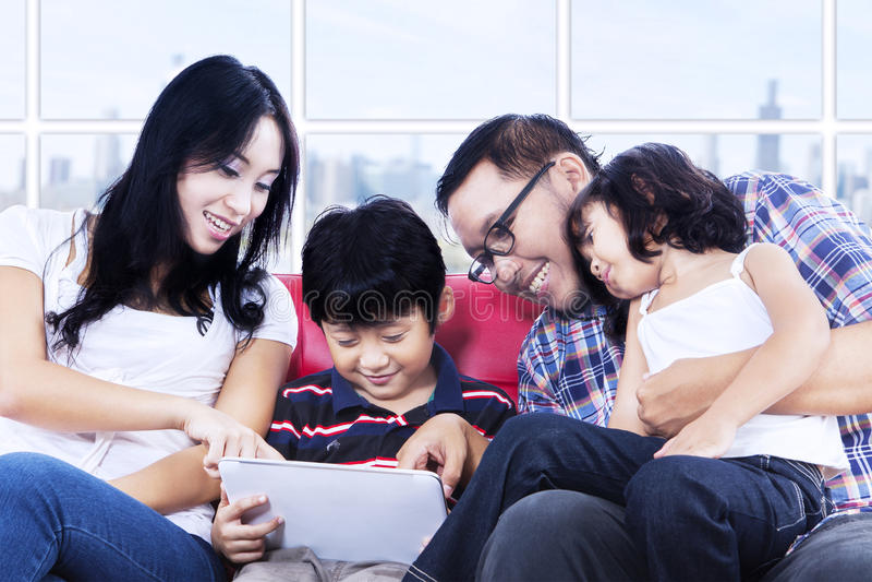 Tiempo de la calidad de la familia usando panel táctil en el apartamento fotografía de archivo