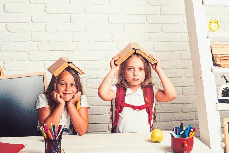 Tiempo de la escuela de muchachas Amistad de peque?as hermanas en sala de clase en el d?a del conocimiento De nuevo a ense?ar del fotos de archivo