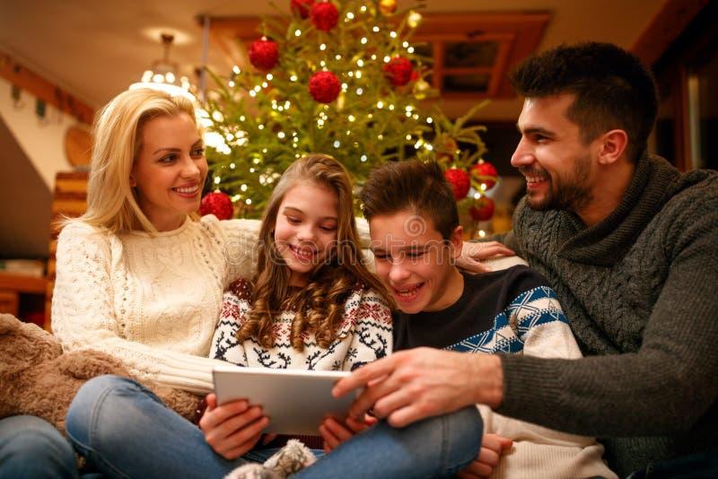 Tiempo de la familia en la Navidad en casa con la tableta digital fotografía de archivo libre de regalías