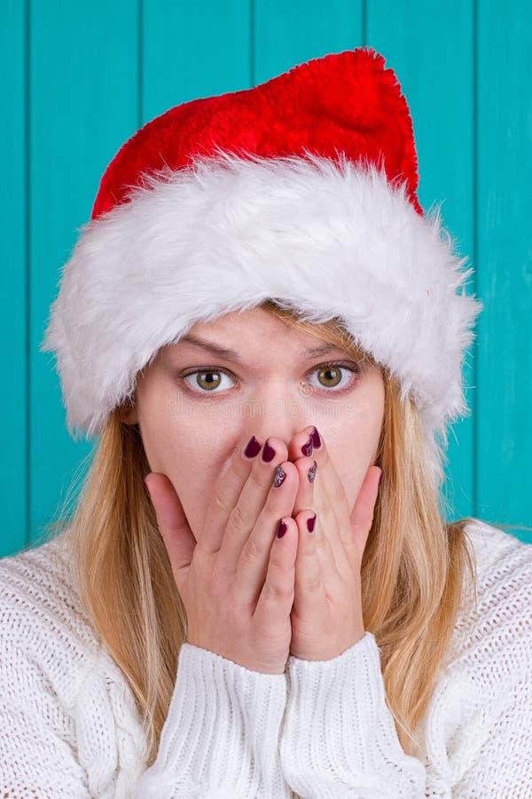 Tiempo de la Navidad Mujer joven que lleva el vestido rojo del sombrero de Papá Noel en fondo azul fotos de archivo