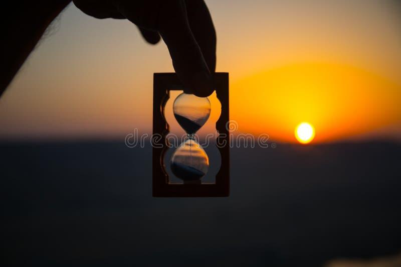 Tiempo de la vida que pasa concepto Mano que sostiene el reloj de arena con el fondo del cielo de la puesta del sol fotografía de archivo libre de regalías