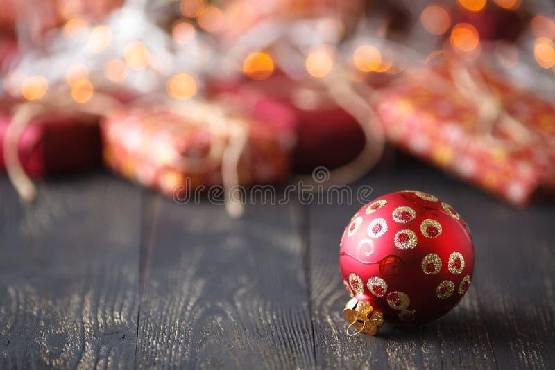 Tiempo de Navidad una bola de la Navidad delante de un manojo de presentes encendido imagen de archivo