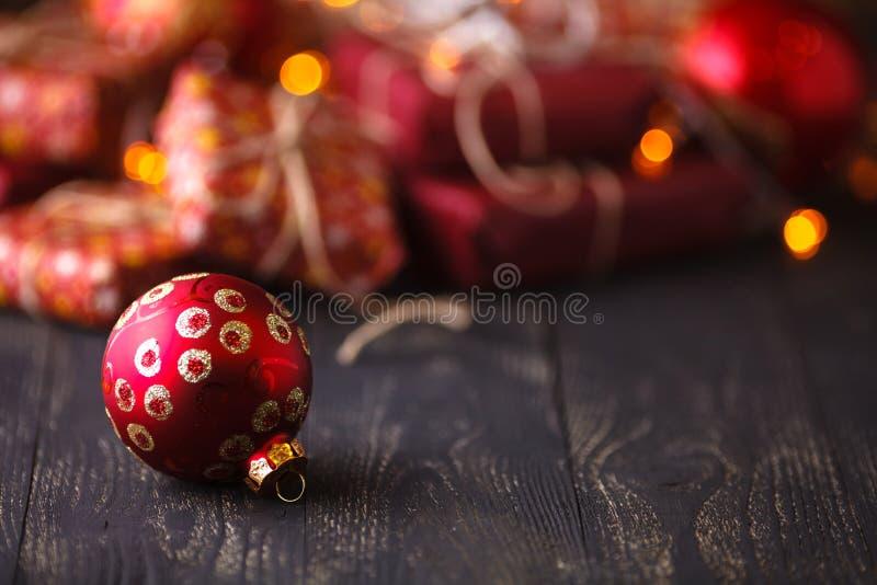 Tiempo de Navidad una bola de la Navidad delante de un manojo de presentes encendido foto de archivo libre de regalías