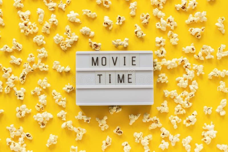 Tiempo de película dispersado de las palomitas y del texto del lightbox en fondo de papel amarillo Plantilla de la visión superio imagen de archivo