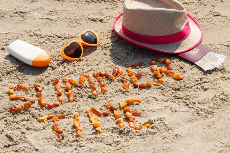Tiempo de verano de la inscripción, accesorios para tomar el sol y pasaporte con las monedas euro en la arena en la playa, tiempo fotos de archivo