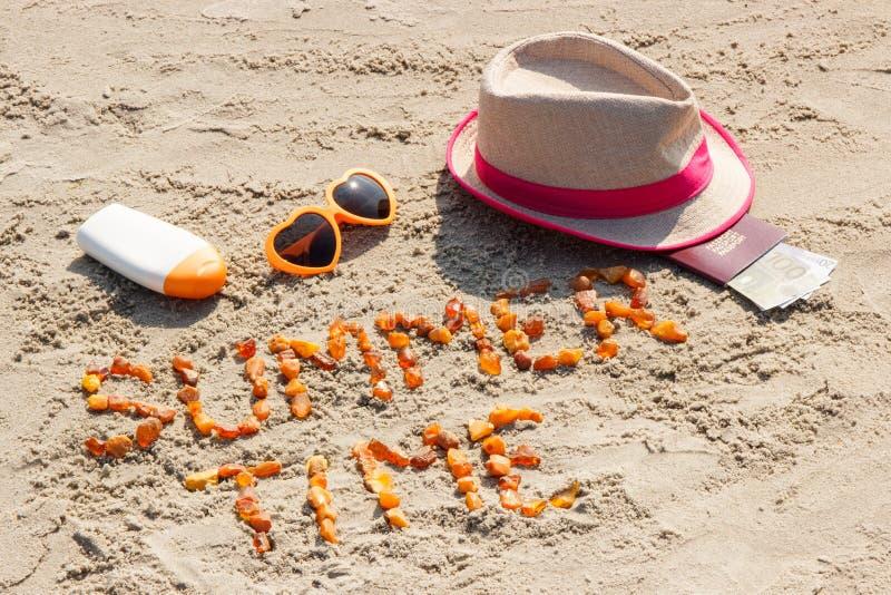 Tiempo de verano de la inscripción, accesorios para tomar el sol y pasaporte con las monedas euro en la arena en la playa, tiempo foto de archivo libre de regalías