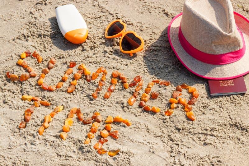 Tiempo de verano de la inscripción, accesorios para tomar el sol y pasaporte en la arena en la playa, tiempo de verano foto de archivo libre de regalías