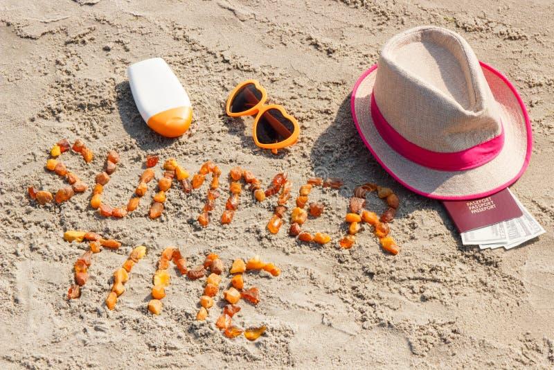 Tiempo de verano de la inscripción, accesorios para tomar el sol y pasaporte con el dólar de las monedas en la arena en la playa fotografía de archivo libre de regalías