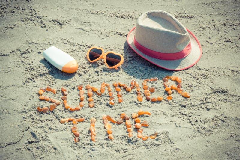 Tiempo de verano de la inscripci?n, gafas de sol, loci?n del sol y sombrero de paja en la arena en la playa imágenes de archivo libres de regalías