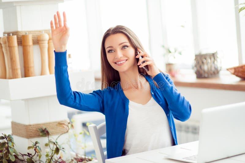 Tiempo del almuerzo ¡Ey allí! La chica joven alegre se está sentando en el café con el ordenador portátil, saludando a su amigo,  foto de archivo